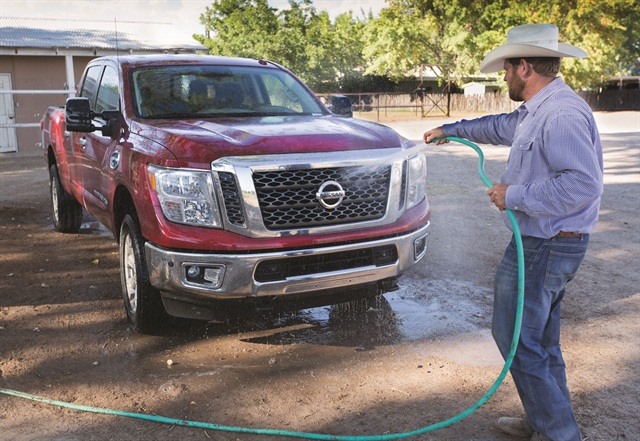 Shain Sproul, a rodeo rider and farmer, washes his three-quarter-ton diesel Nissan Titan XD. He uses his Titan truck to tow a 40-foot stock trailer for 10 horses. Photo by Keith Cizowski, Nissan North America.