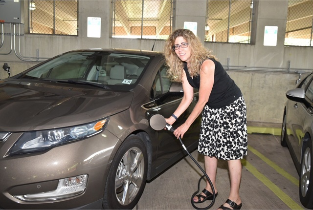 Lee Ann Riccardi, professor of art history and interim director of the college's Center for Global Engagement, plugs in her 2014 Chevy Volt. Photo Courtesy of PSE&G
