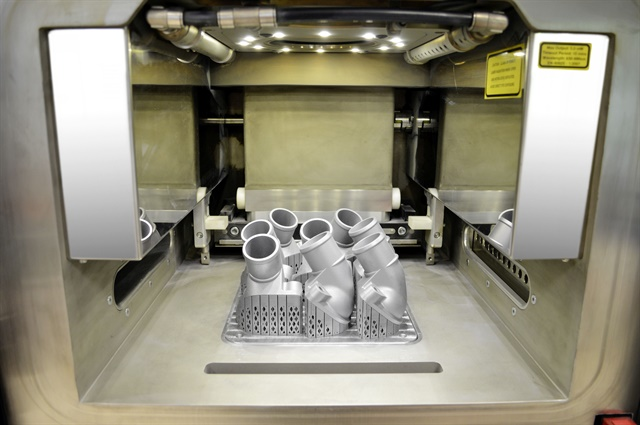 The view into the interior of the 3D printer shows the first printed thermostat covers, which are still connected to the work platform. After removal of the platform and support structure, the aluminium/silicon metallic powder is removed by suction, sieved, cleaned and ecologically fed back into the recycling system. Photo: Daimler