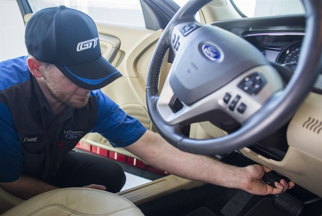 Photo of dealer technician installing FordPass SmartLink OBD-II device courtesy of Ford.