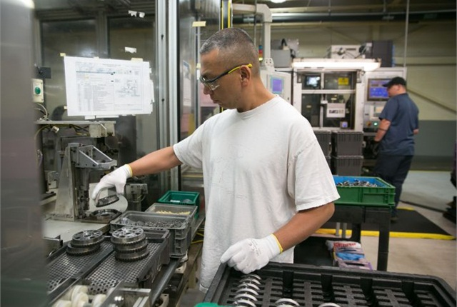 Photo of Grand Rapids worker assembling cam phasers courtesy of GM.