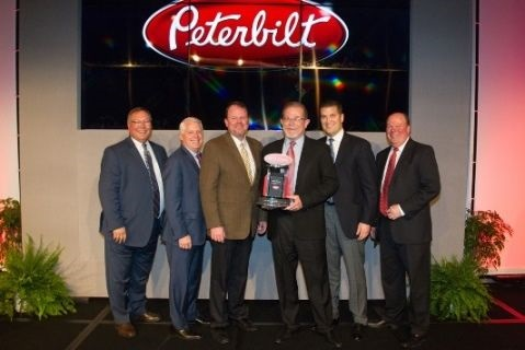 """Rush Enterprises' chairman, CEO and president W.M. """"Rusty"""" Rush, senior vice president and COO Michael J. McRoberts, senior vice present – Peterbilt Dealerships Corey H. Lowe and senior vice president of Retail Sales James E. Thor accepted the award during Peterbilt's annual Dealer Meeting."""