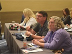 Attendees listen to a speaker at a conference session.